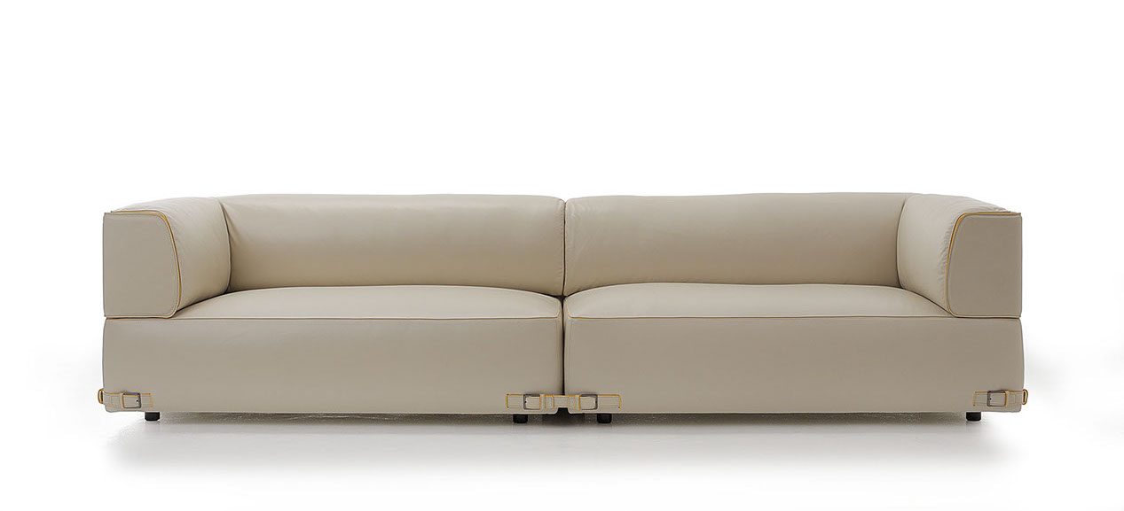 The modernity of the shapes is emphasized by the balanced and harmonic proportions. The frame, with its well-defined traits, features three slim steel profiles in the base running parallel along the entire perimeter. The sofa stands out in terms of the elegant shaped armrest, while soft and rich cushions embrace the large seat.